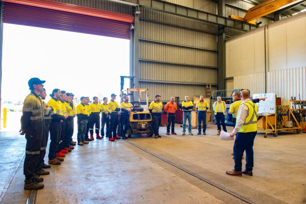 Schlam employees at a warehouse listening to leader